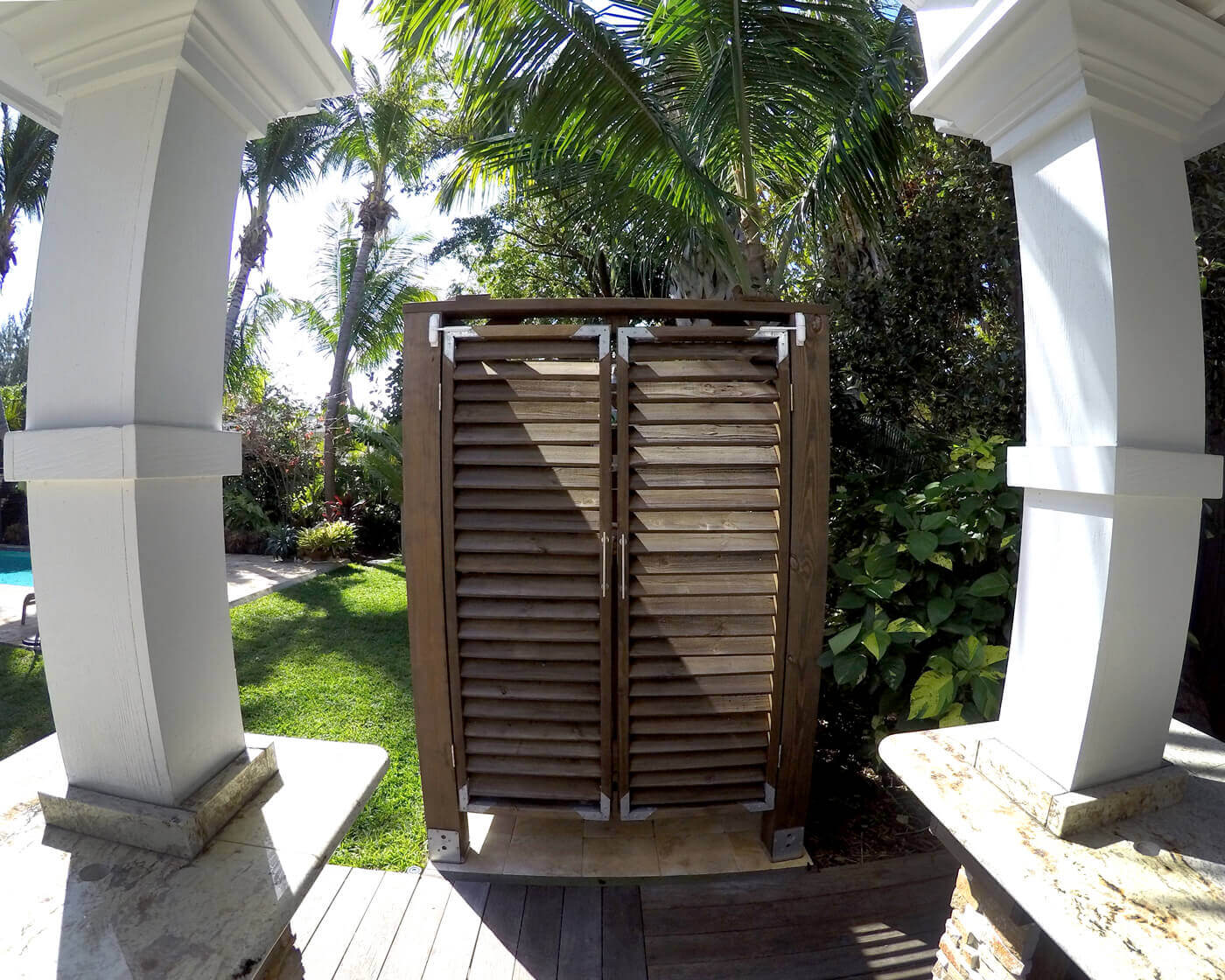 outdoor shower by a pool and columns of outdoor kitchen