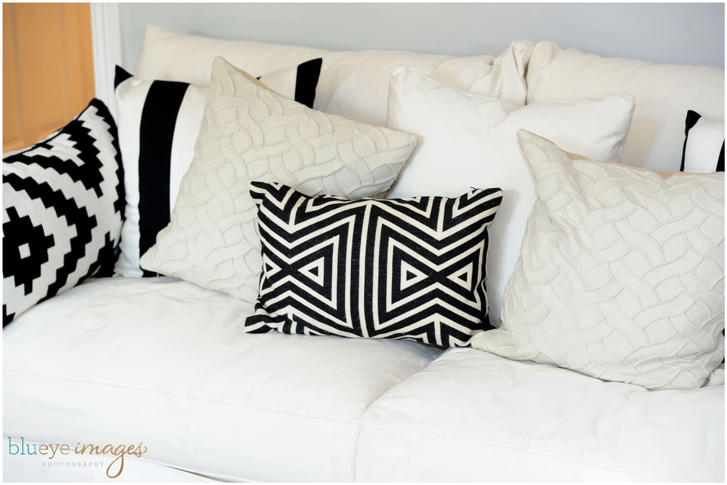 beige couch with black and white geometric-patterned throw pillows